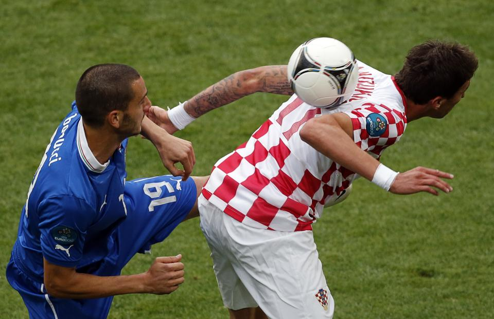 Italy's Antonio Cassano, left, and Croatia's Mario Mandzukic challenge for the ball during the Euro 2012 soccer championship Group C match between Italy and Croatia in Poznan, Poland, Thursday, June 14, 2012. (AP Photo/Anja Niedringhaus)
