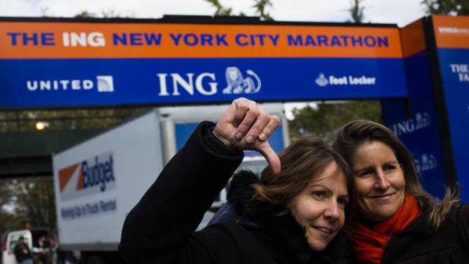 Celine Bally, 42, of French Martinique, gives a thumbs-down in front of the Central Park finish line for the now canceled New York Marathon, Saturday, Nov. 3, 2012, in New York. Bally and her friend Virginia Arminjon, right, also from Martinique, traveled to New York to participate in the footrace and will leave disappointed. Mayor Michael Bloomberg canceled the race after mounting criticism that this was not the time for a race, as the city continues to recover from Superstorm Sandy.(AP Photo/ John Minchillo)