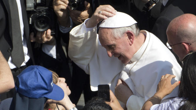 Pope Francis puts on his head a skull cap he was given by young girl, partially seen at left behind blue cap, after stepping out of his pope-mobile to walk the last part of his way to the altar, to deliver his weekly general audience in St. Peter's Square at the Vatican, Wednesday, May, 8, 2013. (AP Photo/Andrew Medichini)