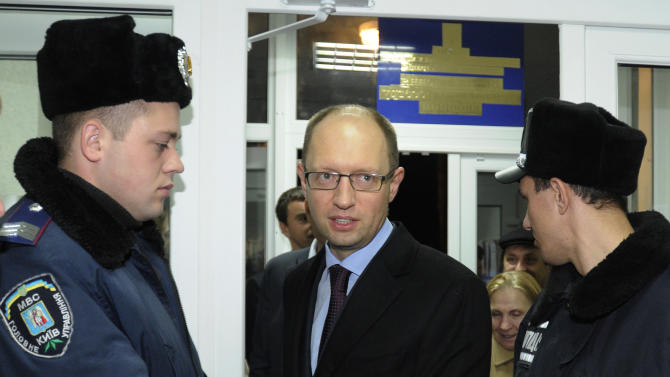 Ukrainian opposition leader Arseniy Yatsenyuk, center, arrives at a district of election commission in Kiev, Ukraine, Tuesday, Oct. 30, 2012. Ukrainian opposition parties on Tuesday appeared split over whether to recognize the ruling party's victory in a parliamentary election denounced as unfair by international observers. (AP Photo/Sergei Chuzavkov)