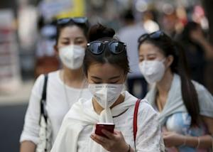 A tourist wearing a mask to prevent contracting Middle East Respiratory Syndrome (MERS) uses her mobile phone at Myeongdong shopping district in central Seoul