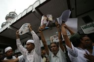Myanmar Muslim men in Yangon on June 5, 2012 hold up pictures of recent violence in western Rakhine state during a gathering. Membres of the Muslim minority protested in downtown Yangon after an angry mob killed 10 Muslims and a crowd attacked a police station in a surge in sectarian tensions in the west of the country