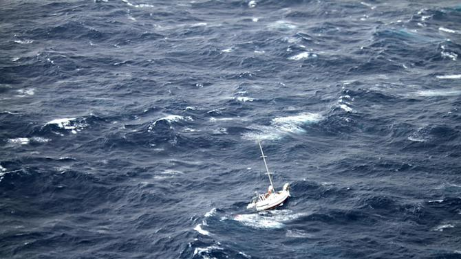 This Sunday, Aug. 10, 2014 photo provided by the U.S. Coast Guard shows the 42-foot sailboat Walkabout caught in Hurricane Julio, about 400 miles northeast of Oahu, Hawaii. Walkabout is disabled and taking on water with three people aboard. The Coast Guard is coordinating the rescue of the boat. (AP Photo/U.S. Coast Guard)