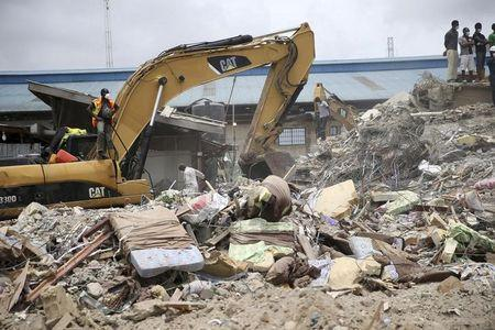 Beds used by guests are seen near an excavator at the site of the collapsed Synagogue Church of All Nations in the Ikotun-Egbe neighbourhood of Nigeria's commercial capital Lagos