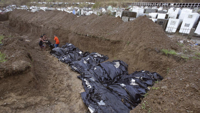Workers arrange body bags at a mass burial site at the Basper public cemetery in Tacloban, Leyte province, central Philippines on Thursday, Nov. 14, 2013. Typhoon Haiyan, one of the strongest storms on record, slammed into 6 central Philippine islands on Friday leaving a wide swath of destruction. (AP Photo/Aaron Favila)
