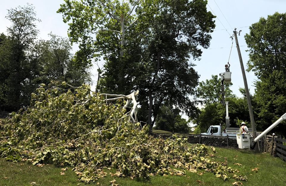 Gulf Power linemen, of Pensacola, Fla., work to repair damaged power lines in Middleburg, Va., Tuesday, July 3, 2012. Severe storms swept through the area leaving many homes and businesses without electricity. (AP Photo/Cliff Owen)