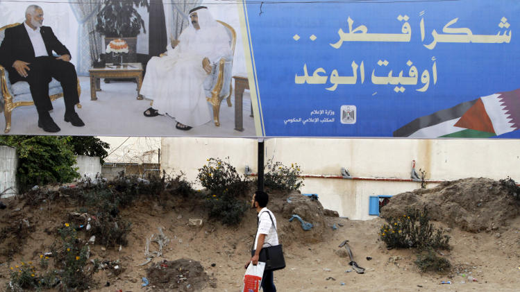 "Palestinian youth walks near a poster of Gaza's Hamas Prime Minister Ismail Haniyeh, left, and Emir of Qatar Sheikh Hamad bin Khalifa al-Thani in Gaza City, Sunday, Oct. 21, 2012. The poster announces the coming visit  of the Emir of Qatar, it reads, ""Thank You Qatar."" (AP Photo/Hatem Moussa)"