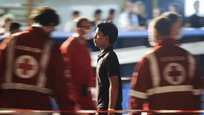 A migrant walks past Red Cross personnel after disembarking from Swedish Coast Guard vessel KBV 001 Poseidon in the Sicilian harbor of Palermo, Italy
