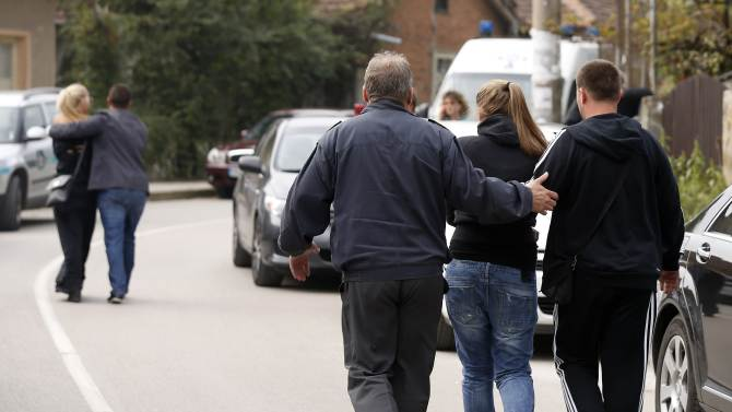 Relatives of victims are comforted  as they walk on a street in the village of Gorni Lom