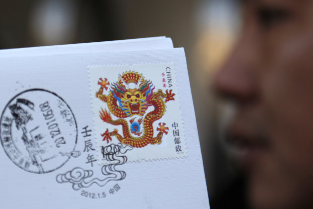 A stamp featuring a dragon is sold with a souvenir envelop and cachets at a post office ahead of the Chinese New Year, or the Year of the Dragon, in Huaibei, in central China's Anhui province, Thursday, Jan. 5, 2012. The stamp designed to depict China's Year of the Dragon and growing confidence that went on sale Thursday has been criticized as looking too ferocious. (AP Photo) CHINA OUT