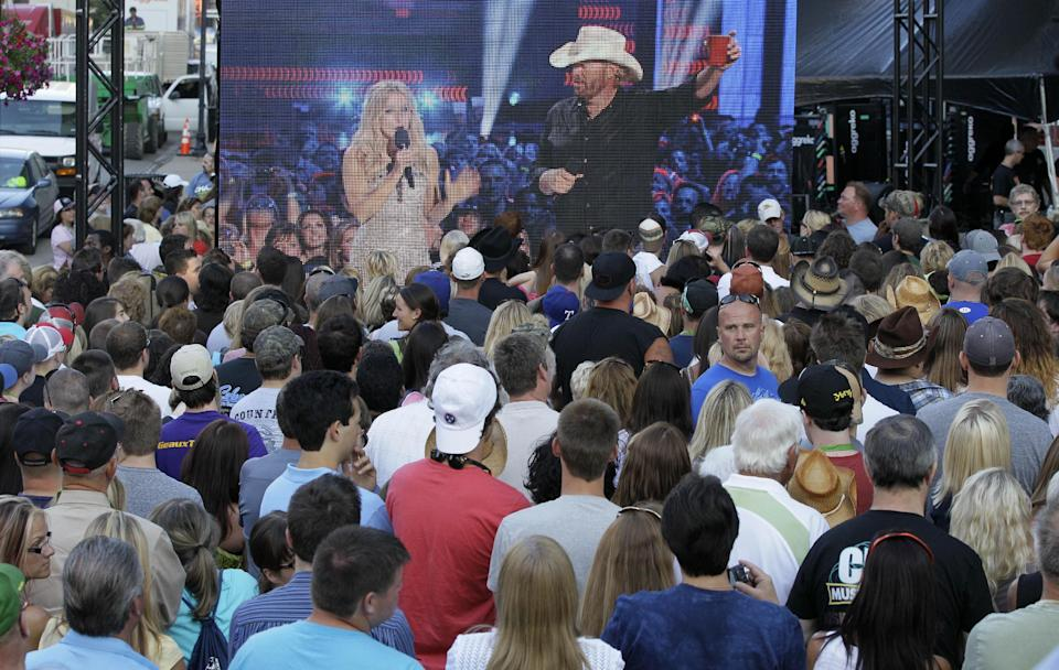 Country music fans watch a big screen projection of Toby Keith and Kristen Bell hosting the CMT Music Awards show as it's shown outside Bridgestone Arena on Wednesday, June 6, 2012, in Nashville, Tenn. (AP Photo/Mark Humphrey)