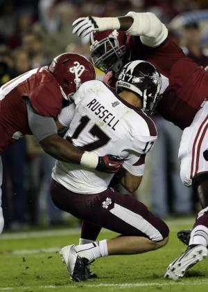 Mississippi State quarterback Dak Prescott (15) is sacked by Alabama linebacker Denzel Devall (30) and defensive lineman Quinton Dial (90) during the first half of an NCAA college football game at Bryant-Denny Stadium in Tuscaloosa, Ala., Saturday, Oct. 27, 2012. (AP Photo/Dave Martin)