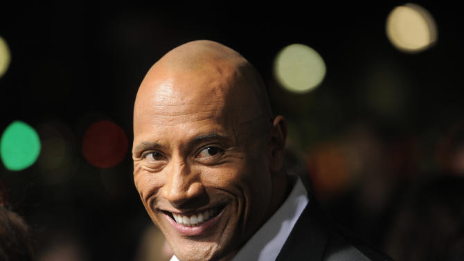 """Dwayne Johnson, a cast member in """"G.I. Joe: Retaliation,"""" looks down the carpet at the Los Angeles premiere of the film at the TCL Chinese Theatre on Thursday, March 28, 2013 in Los Angeles. (Photo by Chris Pizzello/Invision/AP)"""
