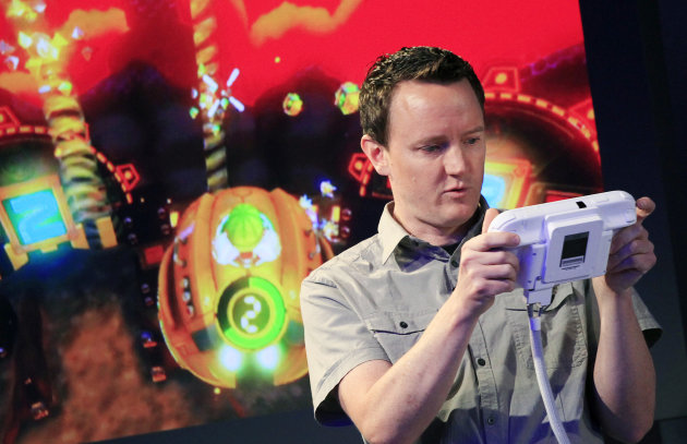 Nintendo&#39;s Bill Trinen demonstrates the Wii U GamePad, Thursday, Sept. 13, 2012 in New York. The gaming console will start at $300 and go on sale in the U.S. on Nov. 18, in time for the holidays, the company said Thursday. (AP Photo/Mark Lennihan)