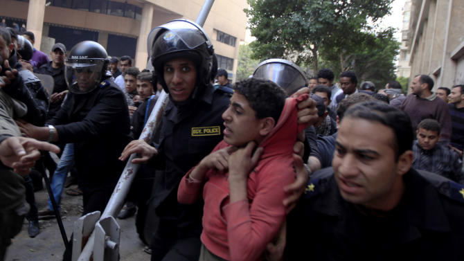 Egyptian riot police arrest a young man during clashes with protesters near Tahrir Square, Cairo, Egypt, Wednesday, Jan. 30, 2013. Egypt's liberal opposition leader called for a broad national dialogue with the Islamist government, all political factions and the powerful military on Wednesday, aimed at stopping the country's eruption of political violence that has left scores dead in the past week. (AP Photo/Khalil Hamra)