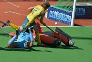 Jacob Whetton of Australia fights his way past defender Manpreet Singh (bottom L) and goalkeeper PT Roa (R) during the semi-final of the Champions Trophy against India. The hosts Australia won 3-0 to reach the final, where they face The Netherlands