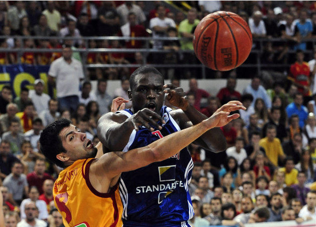 Deng of Britain passes next to Stojanovski of Macedonia during men's European Championship 2011 qualification basketball game in Skopje