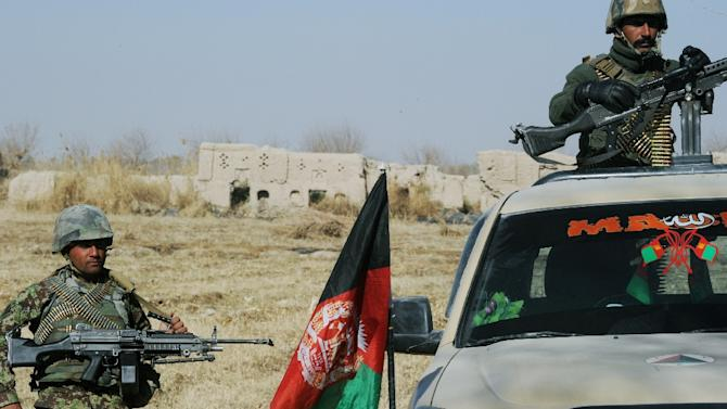 Afghan National Army soldiers keep watch near the remains of the house belonging to Mullah Omar close to the mosque where he founded the Taliban movement, in the village of Sangesar on December 11, 2014