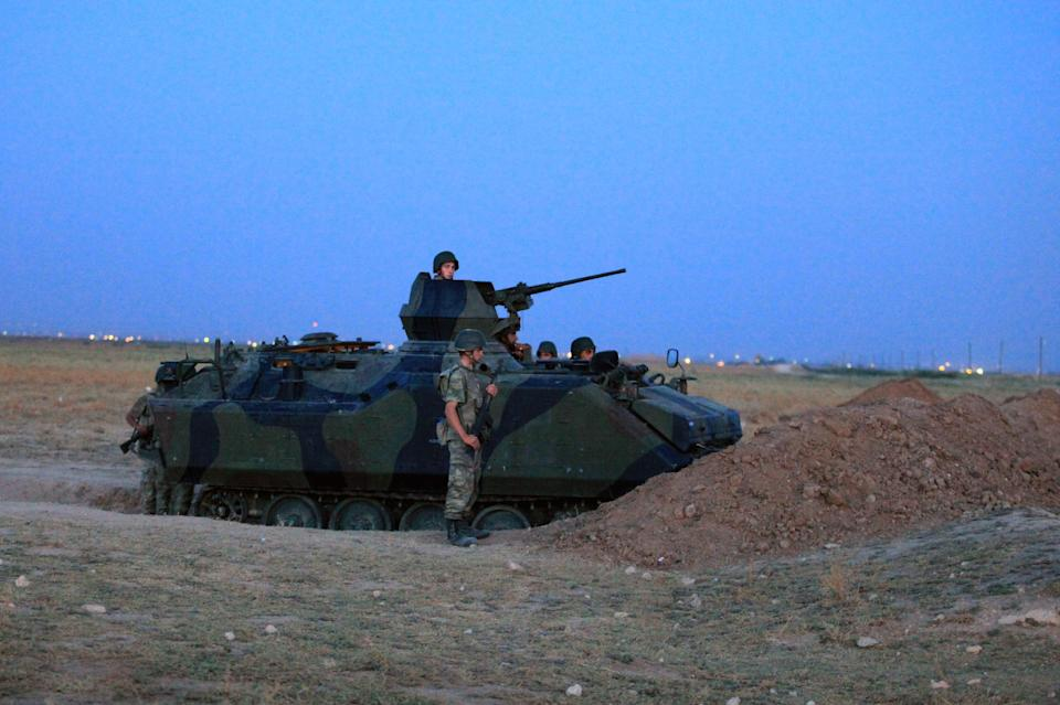 Turkish military stand near the Turkey-Syria border in Akcakale, Turkey, early Friday, Oct. 5, 2012. Turkey fired on Syrian targets for a second day Thursday, but said it has no intention of declaring war, despite tensions after deadly shelling from Syria killed five civilians in a Turkish border town. (AP Photo)