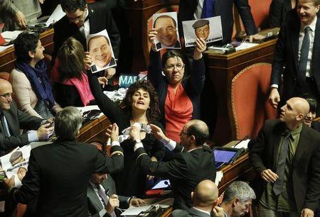 """Opposition senators Moronese and Nugnes of Five Stars Movement hold pictures depicting former Prime Minister Berlusconi and Prime Minister Renzi that read """"Godfathers of Mafia Vote Buying"""" during a vote on reforms at the Senate in Rome"""