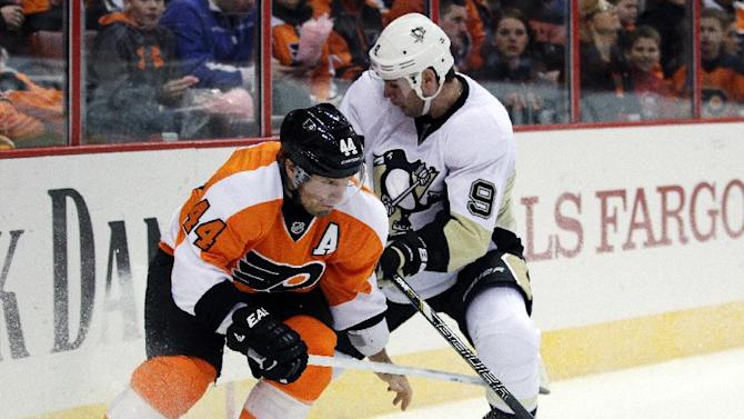 Philadelphia Flyers' Kimmo Timonen, left, loses one of his gloves as he battles for the puck with Pittsburgh Penguins' Pascal Dupuis in the first period of an NHL hockey game, Thursday, March 7, 2013, in Philadelphia. (AP Photo/Tom Mihalek)