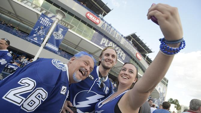 Jessica Wilson, right, takes a picture with Bruce, left, and Barry Ripley outside the arena before Game 1 of the NHL hockey Stanley Cup Final between the Tampa Bay Lightning and the Chicago Blackhawks in Tampa, Fla., Wednesday, June 3, 2015.  (AP Photo/Phelan M. Ebenhack)