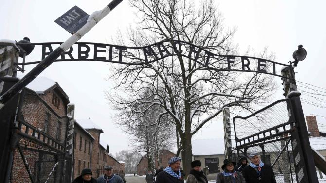 Survivors of the former Nazi German concentration and extermination camp Auschwitz stand at the gate of the former camp in Oswiecim