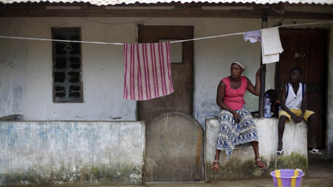 Neighbors sit in front of the house that Thomas Eric Duncan, a Liberian man now hospitalized in Texas, rented on 72nd SKD Boulevard during his stay in Liberia, in Morovia, Thursday Oct. 2, 2014. Since the announcement of his illness, Duncan has become a symbol of how Ebola could spread within the United States. Here in Liberia, though, he is just another neighbor infected by a virulent Ebola cluster ravaging this neighborhood of tin-roof homes along 72nd SKD Boulevard.(AP Photo/Jerome Delay)