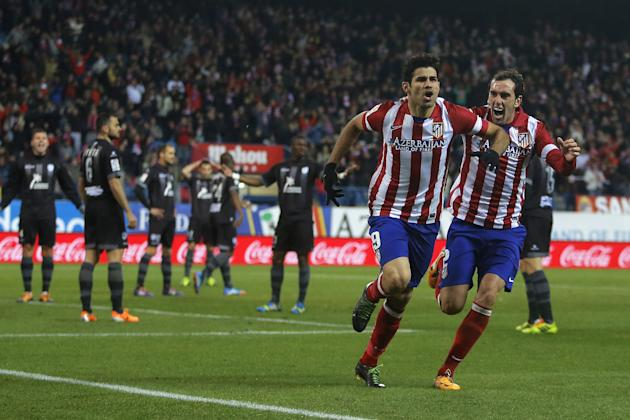Atletico's Diego Costa, second right, celebrates his goal with Diego Godin, right, during a Spanish La Liga soccer match between Atletico de Madrid and Levante at the Vicente Calderon stadium in M
