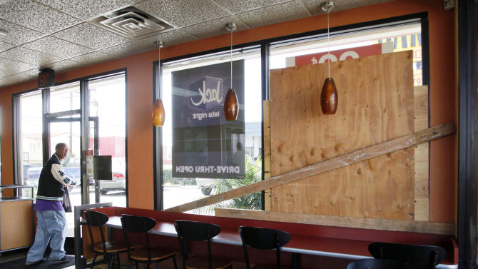 A fast food restaurant shows boarded up windows that were broken after a protest Monday night in Los Angeles Tuesday, July 16, 2013. Protesters ran through Los Angeles streets Monday night, breaking windows, attacking people on sidewalks and raiding a Wal-Mart store, while others blocked a major freeway in the San Francisco Bay area in the third night of demonstrations in California over George Zimmerman's Florida acquittal in the killing of Trayvon Martin. (AP Photo/Nick Ut)