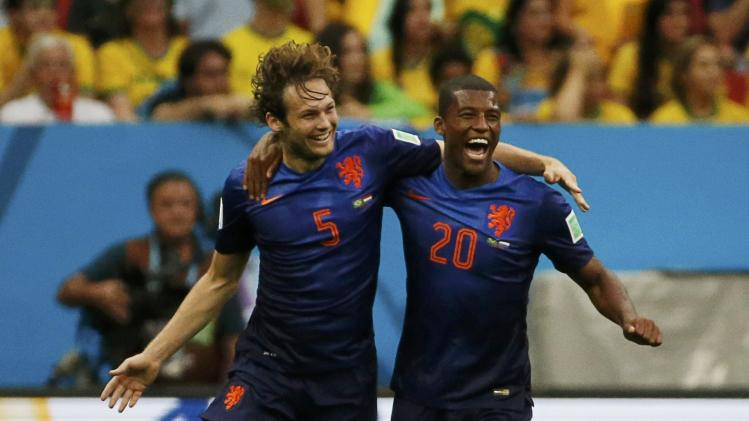 Blind of the Netherlands celebrates with Wijnaldum after scoring against Brazil during their 2014 World Cup third-place playoff at the Brasilia national stadium in Brasilia
