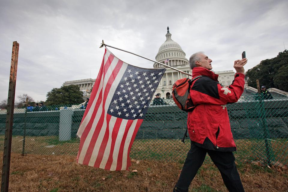 Rit Picone of Newpaltz, N.Y., carries an American flag upside down as a symbol of protest as demonstrators aligned with the Occupy Wall Street movement gathered on Capitol Hill in Washington, Tuesday, Jan. 17, 2012,  to decry the influence of corporate money in politics.  (AP Photo/J. Scott Applewhite)