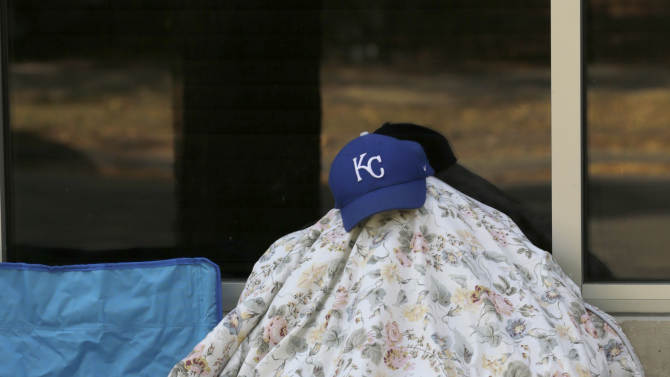 Terrance Kennedy sleeps under blanket and his Kansas City Royals baseball cap as he waits in line for Hot Doug's gourmet hot dog stand to open Wednesday, Oct. 1, 2014, in Chicago. When owner Doug Sohn announced this year he was closing in October, there was little doubt that encased meat aficionados would turn up for one last sausage made of everything from escargot to foie gras to Portuguese linguisa. A line that starts forming deep into the night is lined with lawn chairs, card tables, poker chips, sleeping bags, favorite pillows, more than a few bottles of booze and anything else to help a couple hundred people get through a wait of eight, nine or ten hours. (AP Photo/Charles Rex Arbogast)