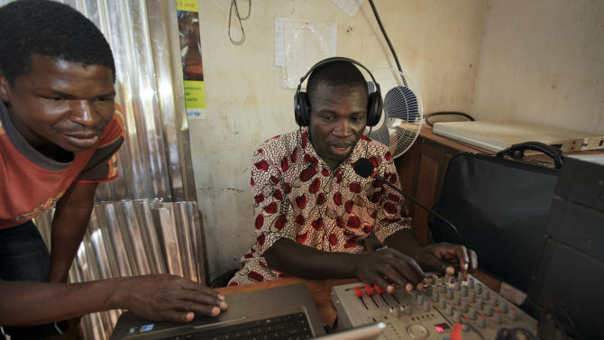 Ricardo Dimanche, center, director of the tiny radio station Radio Zereda, which translates as Radio Peace and which is powered by solar panels and  was partially built with U.S. funds to transmit its message, works at the station in Obo, Central African Republic, Sunday, April 29, 2012. Obo was the first place in the Central African Republic that Joseph Kony's Lord's Resistance Army (LRA) attacked in 2008 and today it's one of four forward operating locations where U.S. special forces have paired up with local troops and Ugandan soldiers to seek out Kony. (AP Photo/Ben Curtis)