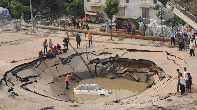 A stranded car is hoisted from a collapsed road surface in Guangzhou