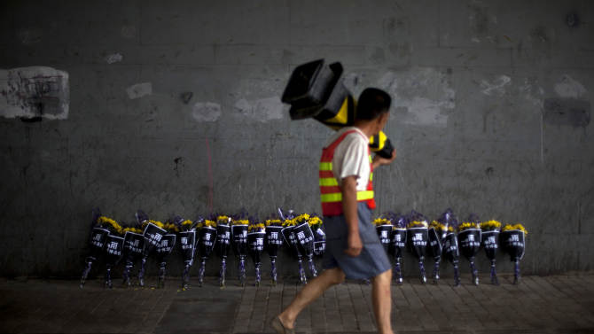 "A roadworker walks past flowers placed under a bridge where a man drowned on Saturday, July 21 in his flooded car on a main road in Beijing Friday, July 27, 2012. Chinese characters on the wraps read ""One Rain, One Day of Mourning."" The storm that ravaged Beijing nearly a week ago and killed at least 77 people remains a sensitive topic in China, with a newspaper ordered to cut its coverage and online discussions curtailed. (AP Photo/Alexander F. Yuan)"