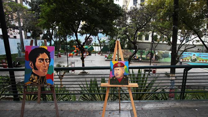 Portraits of Venezuela's independence hero Simon Bolivar, left, and Venezuela's President Hugo Chavez are exhibited for sale on folding easels in Caracas, Venezuela, Friday, Dec. 28, 2012. The obsessive, circular conversations about Chavez's health dominate family dinners, plaza chit-chats and social media sites in this country on edge since its larger-than-life leader went to Cuba for emergency cancer surgery more than two weeks ago. The man whose booming voice once dominated the airwaves for hours at a time has not been seen or heard from since.(AP Photo/Fernando Llano)