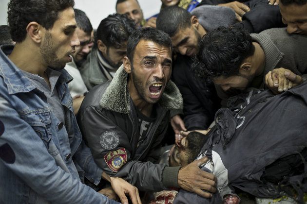 A Palestinian man cries next the body of a dead relative in the morgue of Shifa Hospital in Gaza City, Sunday, Nov. 18, 2012. President Barack Obama on Sunday defended Israel's airstrikes on the Gaza