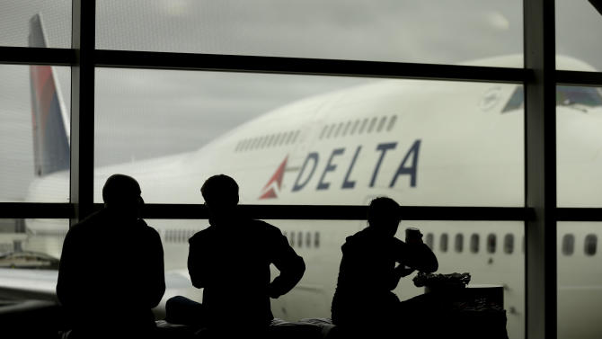 Travelers on Delta Airlines waits for flights Monday, Oct. 29, 2012, in Detroit. Dozens of departing flights have been canceled at Detroit Metropolitan Wayne County Airport as a looming superstorm locks down flights to the East Coast. Hurricane Sandy continued on its path Monday, as the storm forced the shutdown of mass transit, schools and financial markets, sending coastal residents fleeing, and threatening a dangerous mix of high winds and soaking rain.(AP Photo/Charlie Riedel)