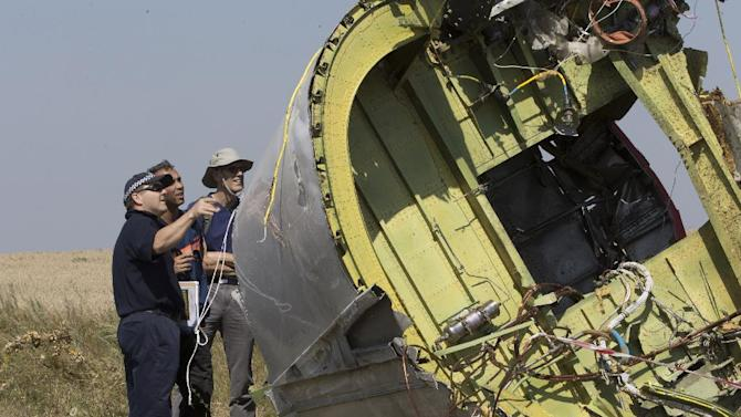 Australian and Dutch experts examine a piece of the Malaysia Airlines Flight 17 plane, near the village of Hrabove, Donetsk region, eastern Ukraine Friday, Aug.1, 2014. The investigators from the Netherlands and Australia plus officials with the Organization for Security and Cooperation in Europe traveled from the rebel-held city of Donetsk in 15 cars and a bus to the crash site outside the village of Hrabove. Then they started setting up a base to work from at a chicken farm. The investigative team's top priority is to recover human remains that have been rotting in midsummer heat of 90 degrees (32 degrees Celsius) since the plane went down on July 17. (AP Photo/Dmitry Lovetsky)