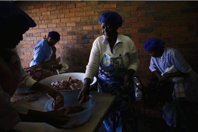 Women prepare food to be eaten after a service for former South African President Nelson Mandela, at the Regina Mundi Church in Soweto