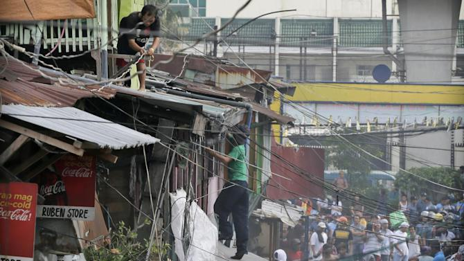 A demolition crew begins to tear down a squatters' community at suburban Caloocan city, north of Manila, Philippines Tuesday, May 26, 2015. Population growth, poverty and lack of economic opportunities in rural areas have driven millions of Filipinos to urban areas, many settling in squatters' colonies that dot the sprawling metropolitan area in and around Manila. Most of the land they occupy is privately owned, and clearing the dwellings often result in violence. According to a residents, the area is home to approximately 500 families, with some having lived there for 50 years. (AP Photo/Bullit Marquez)