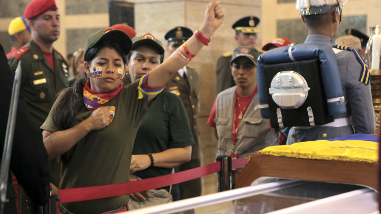 In this photo released by Miraflores Press Office, a woman pays her respects as she files past the glass-topped casket containing the remains of Venezuela's late President Hugo Chavez lying in state at the military academy in Caracas, Thursday, March 7, 2013. Chavez died of a massive heart attack Tuesday after great suffering and inaudibly mouthed his desire to live, the head of Venezuela's presidential guard said late Wednesday. (AP Photo/Miraflores Presidential Press Office)