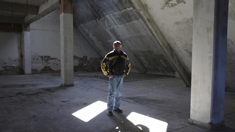 """Bosnian man Mladen Popovic, 34, looks on inside of closed and abandoned factory in the Bosnian town of Drvar, some 400 Km (250 miles) west of Sarajevo, on Monday, March 4, 2013.  With candles, speeches and an obituary plastered on walls reading """"Town of Drvar 1883 - 2013,""""  the residents symbolically laid this town to rest in peace on Monday. Two months ago, the last company in Drvar closed down, sending the town's unemployment rate skyrocketing to around 80 percent.  The town had no chance to survive the double tragedies of the 1992-95 Bosnian war and then the global financial crisis which have joined to kill off this once lively metropolis.(AP Photo/Amel Emric)"""