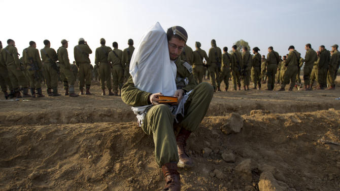 An Israeli officer holds a Torah scroll as he reads from a holy book while others gather in a staging area near the Israel Gaza Strip Border, southern Israel, Monday, Nov. 19, 2012.  The Palestinian civilian death toll mounts as Israel ferociously pursues Gaza Strip militants who are menacing nearly half of Israel's population with rocket fire. (AP Photo/Ariel Schalit)