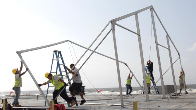 Construction workers disassemble a temporary building on the beach that was set up for an upcoming surfing competition in Long Beach, N.Y., Thursday, Aug. 25, 2011. The building was being being taken down to over concerns that it lies in the path of Hurricane Irene, which is threatening to hit the East Coast. (AP Photo/Seth Wenig)