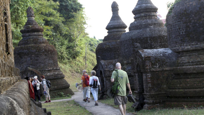 FILE - In this Nov. 8, 2012 file photo, tourists walk amongst ancient Pagodas in Mrauk U, Rakhine state, western Myanmar. In the west, terrified villagers fled burning homes in an explosion of ethnic and religious violence. In the north, refugees from a civil war cower in chilly camps, desperately short on life's basic necessities. And in dank jails, hundreds of political prisoners languish behind bars, wondering when they'll ever be freed.  This is Myanmar, the country hailed by the West for its stunning democratic transformation since last year. It still has reams of unfinished business, little of which will be seen by President Barack Obama when he becomes the first American head of state to visit the country's pagoda-studded main city on Monday, Nov. 19, 2012. (AP Photo/Khin Maung Win)