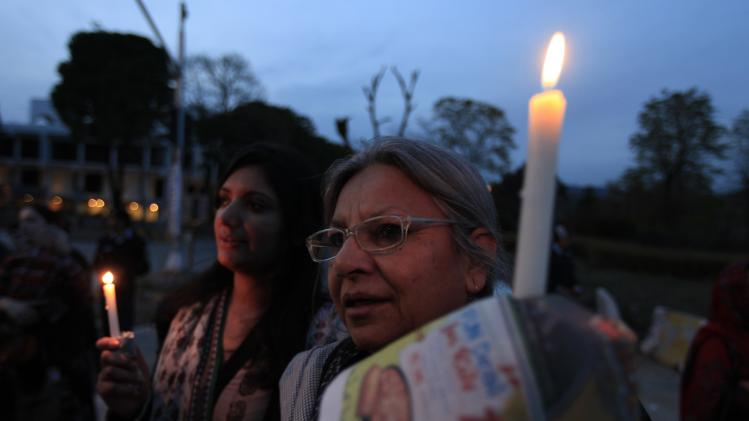 Woman holds a candle as she takes part in a candlelight vigil to mark women's day in Islamabad