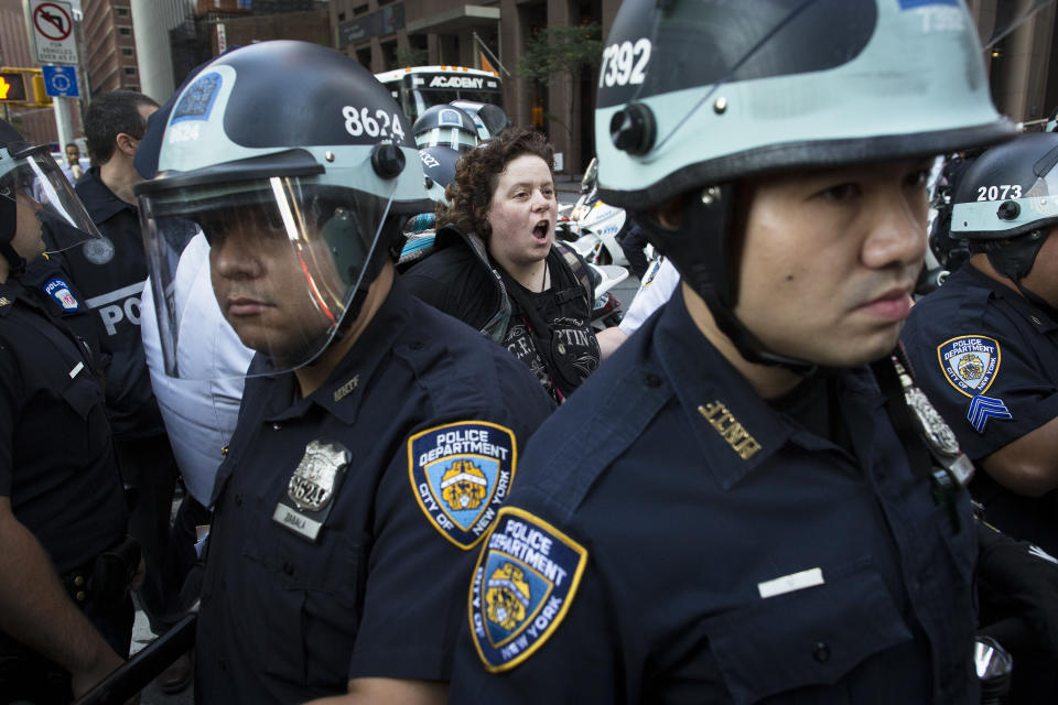 A photographer is arrested during an Occupy Wall Street march as police stand guard, Monday, Sept. 17, 2012, in New York. A handful of Occupy Wall Street protestors have been arrested during a march toward the New York Stock Exchange on the anniversary of the grass-roots movement. (AP Photo/John Minchillo)