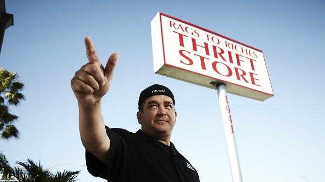 This 2011 photo released by A&E shows Dave Hester in front of the Rags to Riches thrift store in Costa Mesa, Calif.  Hester sued A&E Television Networks on Tuesday, Dec. 11, 2012, claiming he was fired from the show after complaining that producers had planted valuable items in some of the lockers featured on the reality series. (AP Photo/A&E)